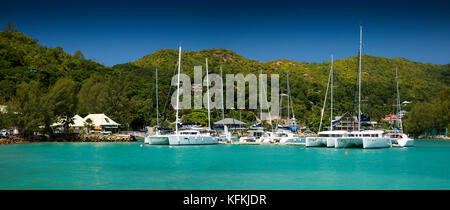 The Seychelles, Praslin, Baie St Anne, jetty, charter boats moored in sheltered harbour, panoramic - Stock Photo