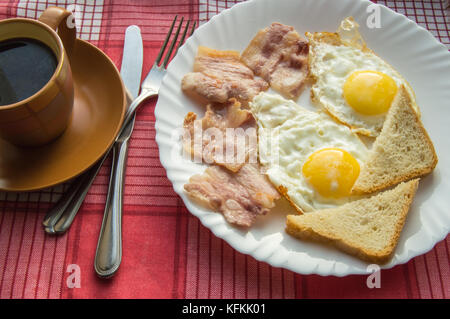 Delicious Breakfast - a Cup of coffee, a plate of fried eggs, bacon and toast, next to the Cutlery on red checkered - Stock Photo