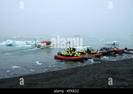 Tourists in zodiac boats leaving shore on Jokulsarlon glacial lagoon tour viewing icebergs wearing bright yellow - Stock Photo