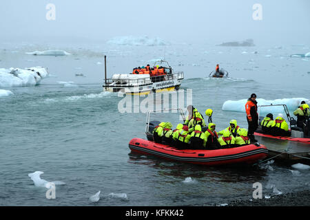 Tourists in zodiac boats leaving shore Jokulsarlon glacial lagoon tour, wintery day viewing icebergs wearing bright - Stock Photo