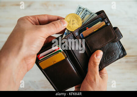 hand put bitcoin in the wallet - Stock Photo