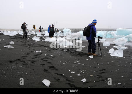 Photographers on photo tour with cameras and tripods standing and photographing icebergs washed up on black sand - Stock Photo