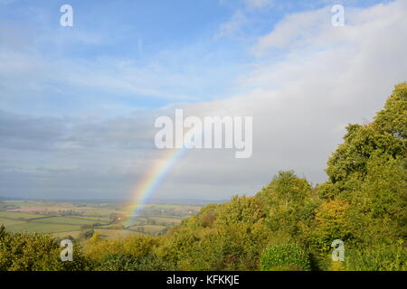 A rainbow in autumn blue sky in South Herefordshire countryside looking out from hill side with clouds trees and - Stock Photo