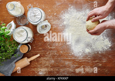 hands kneading pasta dough flour and kitchen utilities on wooden workspace - Stock Photo