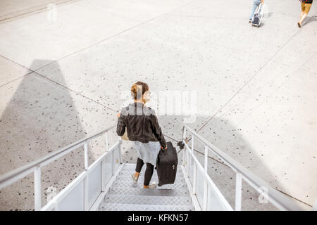 Woman walking out the airplane - Stock Photo