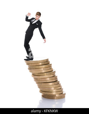 Full length of businessman balancing on stacked coins against white background - Stock Photo