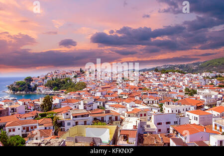 Sunset over Skiathos town on Skiatos Island, Greece. Beautiful view of the old town with boats in the harbour. - Stock Photo