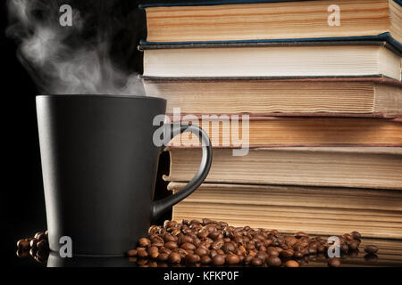 Large black coffee cup with steam and old books on black table. Selective focus - Stock Photo