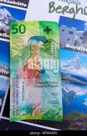 ST. NIKLAUS, SWITZERLAND - Swiss franc note with image of paraglider, 50 CHF, in front of tourism guide. - Stock Photo