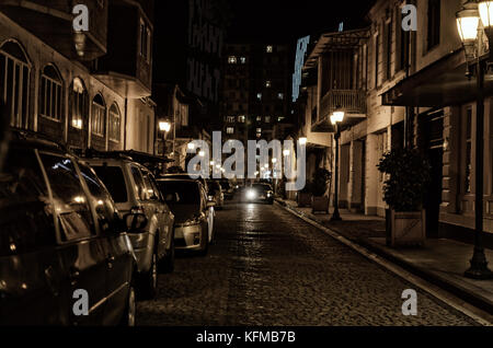 Street of the old night city with paving stone, lit by street lamps with parked cars. - Stock Photo