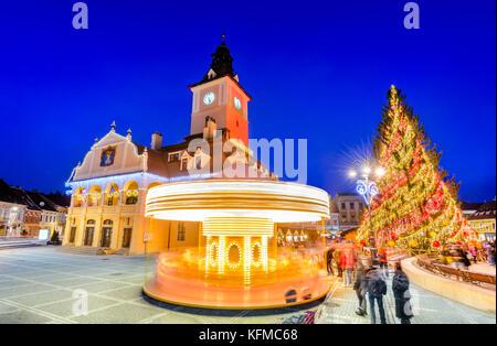 Brasov, Romania. Christmas Market in Main Square, with Xmas Tree and lights. Transylvania landmark. - Stock Photo