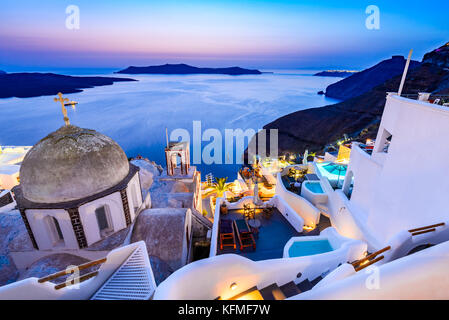 Fira, Santorini - Greek Islands landmark with white village, cobbled paths, greek orthodox blue church and sunset - Stock Photo