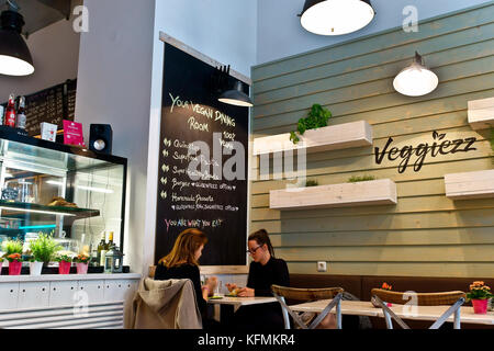 Friends, two girls having lunch at Veggiezz all vegan restaurant. Vienna, Wien, Austria, Europe - Stock Photo