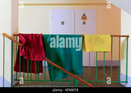 Laundry on stairs railing, colored bath towels on stairs railing inside an old Viennese condominium. Vienna, Austria,Europe - Stock Photo