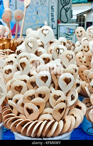 Wooden spoons with carved heart shape on display in a stall at the market. Stack of handcrafted organic cooking - Stock Photo