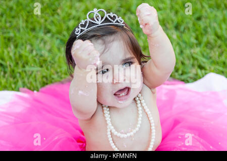 Happy excited baby toddler girl first birthday anniversary party. Shouting hooray with raised fists in joy. Face - Stock Photo