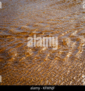 Sunlight on running tannin water ripple background - Stock Photo