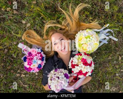 Stunning teen girl portrait from above on greenfield surrounded by flowery bouquets smiling happiness looking at - Stock Photo