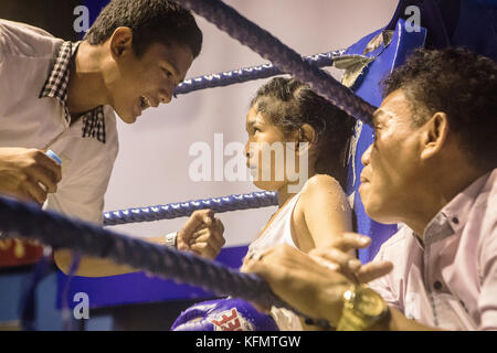 Hasana, 7 years old and 7 matches, muay Thai fighter sitting in the conner of the ring, advised by his coaches, - Stock Photo