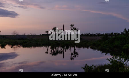 Sunset with clouds reflecting in a pond at Merritt Island National Wildlife Refuge, Florida, USA - Stock Photo