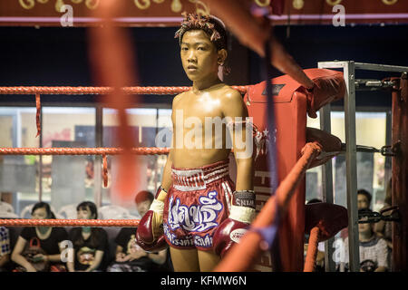 Portrait. Boy, Muay Thai boxer before the fight starts, Bangkok, Thailand - Stock Photo