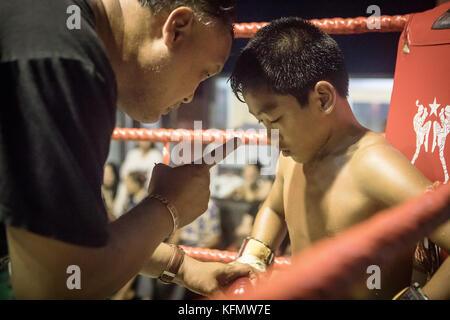 Young Thai boxing sitting in the conner of the ring, advised by his coach, between rounds, Bangkok, Thailand - Stock Photo