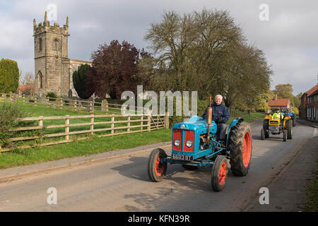 Man driving old blue vintage tractor through village of Bugthorpe on Wolds Vintage Group Road Run, an annual charity - Stock Photo
