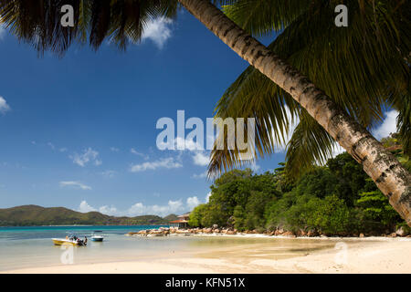 The Seychelles, Praslin, Anse Posession, palm fringed beach and Coin d'Or Guest House on headland - Stock Photo