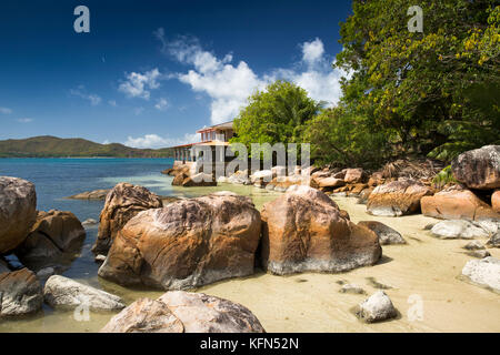 The Seychelles, Praslin, Anse Posession, Coin d'Or Guest House on headland beyond rocks - Stock Photo