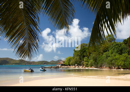"""The Seychelles, Praslin, Anse Posession, palm fringed tropical beach with Coin d""""Or Guest House on headland - Stock Photo"""
