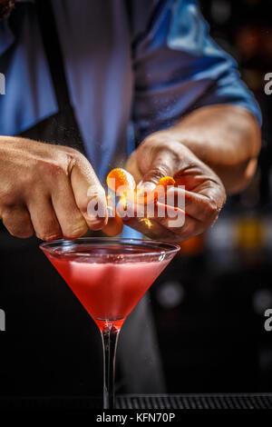 Expert barman is decorating cosmopolitan cocktail with orange peel - Stock Photo