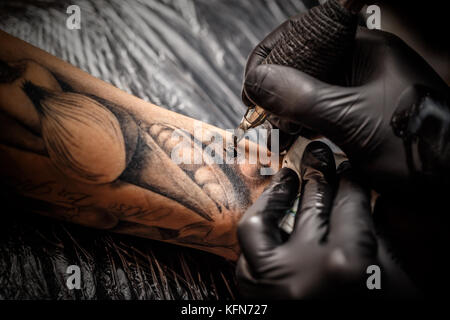 A professional tattoo artist introduces black ink into the skin using a needle from a tattoo machine. - Stock Photo