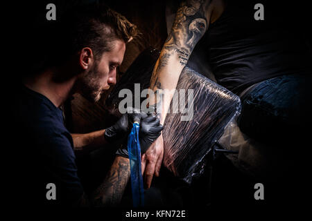 The bearded tattoo artist makes a tattoo on a man's hand - Stock Photo