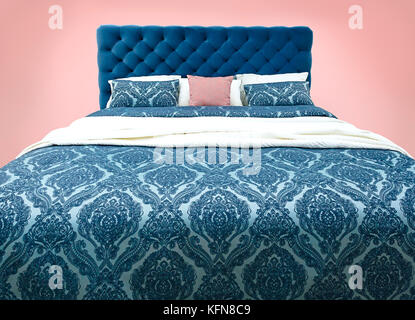 Blue bed furniture with patterned bed linen . Soft velour fabric bed. Classic modern furniture on isolated background - Stock Photo