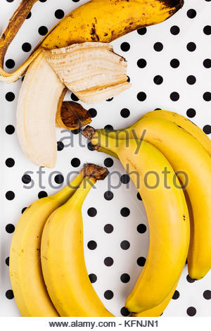 Overhead view of one overripe peeled banana together with a small bunch of ripe bananas on a polka dot background. - Stock Photo