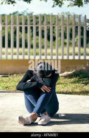 Young woman outdoor hunched up and seated outdoor on the floor, taking a break under the morning sunlight, her cell - Stock Photo