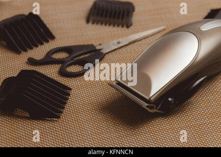Stylish Professional Hair Clippers, accessories on brown background - Stock Photo