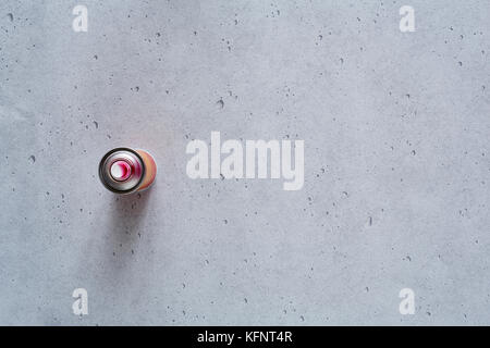 single pink spray can on concrete - Stock Photo