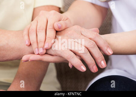 Close-up Of Doctor Holding Hand Of Patient - Stock Photo