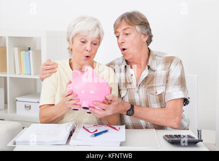 Portrait Of Senior Couple Saving Money In The Pink Piggybank - Stock Photo