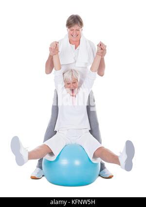 Happy Senior Couple Exercising With Fitness Ball On White Background - Stock Photo
