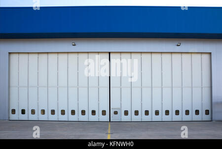 Airport hangar from the outside with big tall doors. Front view. - Stock Photo