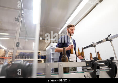 men with bottles on conveyor at craft beer brewery - Stock Photo