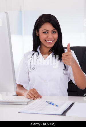 Happy Female Doctor Using Computer And Gesturing Thumbs-Up Sign - Stock Photo
