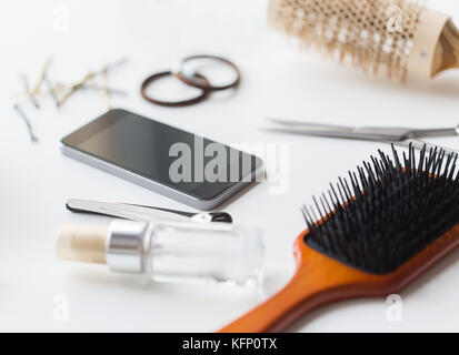 smartphone, scissors, brushes and other hair tools - Stock Photo