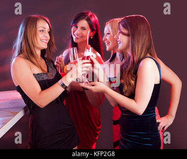 Group of four happy beautiful young female friends celebrating in a nightclub with glasses of cocktail in their - Stock Photo
