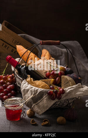 Picnic basket with cheese, fruits, bread and wine - Stock Photo