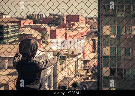 Lonely boy standing on top of the roof behind the fence - Stock Photo