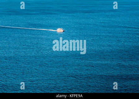 Small white boat on calm blue ocean. Scenic ocean panorama, a boat on Pittwater, in Sydney, Australia. - Stock Photo