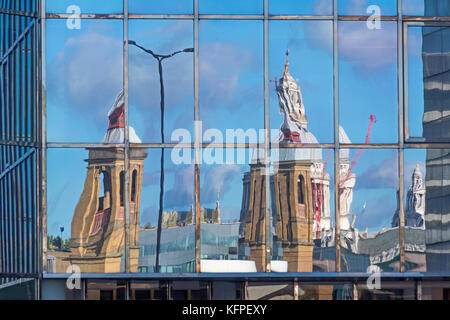 A distorted image of Cannon Street station and St Paul's Cathedral reflected in the glass frontage of an office - Stock Photo